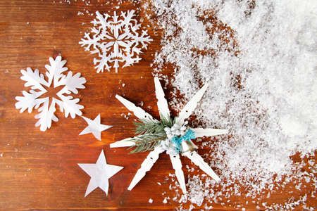 Beautiful snowflakes with snow on wooden background photo