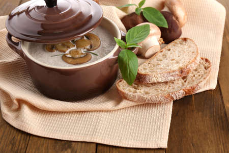 Mushroom soup in pot, on wooden background Stock Photo - 27677528