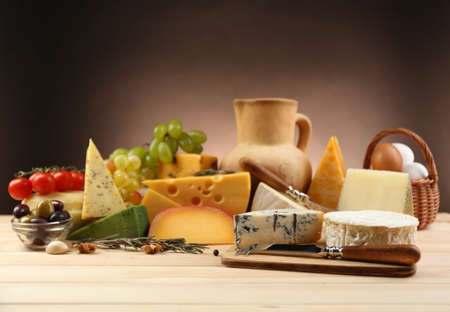 chees: Tasty dairy products on wooden table, on dark background