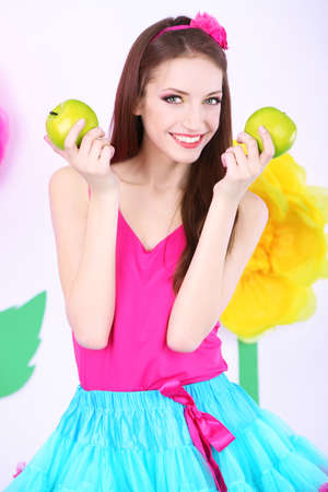 Beautiful young woman in petty skirt with apples on decorative  photo