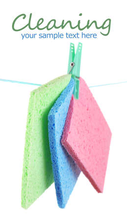 Kitchen sponges hanging on rope isolated on white photo