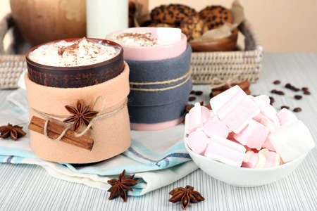 Mug of hot drink decorated in felt on wooden table photo