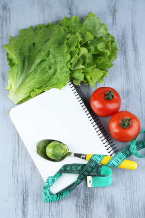 Notebook with measuring tape and vegetables on wooden background photo