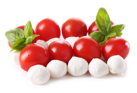 Tasty mozzarella cheese balls with basil and red tomatoes, isolated on white photo