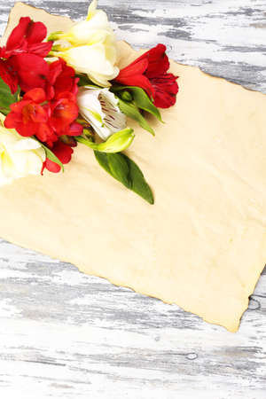 Beautiful Alstroemeria flowers and empty sheet on wooden table photo
