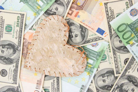 Love and money concept. Heart on European and American money