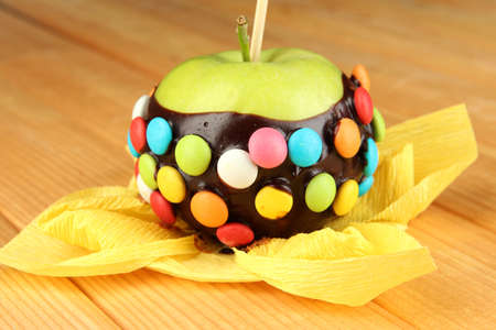 Candied apple on stick on wooden table photo