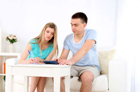 Young couple calculating finance at desk, on home interior  photo