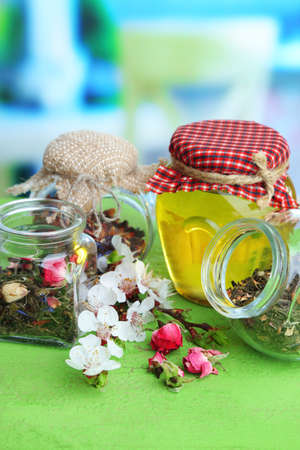 Assortment of herbs and tea and honey in glass jars on wooden table, on bright background  photo