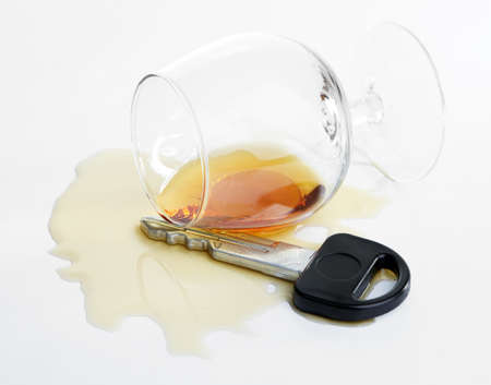 Composition with car key and glass of cognac, isolated on white photo