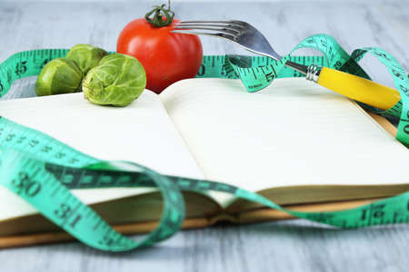 Book with measuring tape and vegetables on wooden background photo