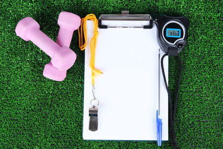 Sheet of paper and sports equipment on grass close-up photo