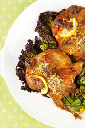 Roasted quails with vegetables on plate, on wooden background photo