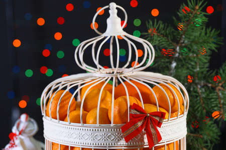Tangerines in decorative cage with Christmas decor, on shiny background photo