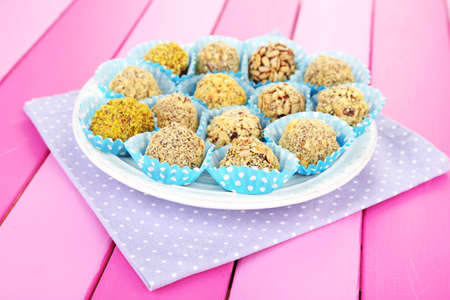 Set of chocolate candies, on wooden background photo