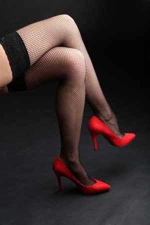 Stockings on perfect woman legs on dark background photo
