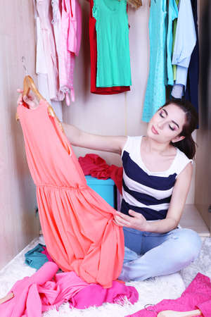 Beautiful young woman sitting on floor near wardrobe in room photo