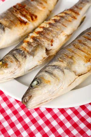 pescado frito: Pescado a la parrilla en un plato delicioso en la mesa de close-up Foto de archivo
