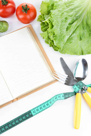 Cutlery tied with measuring tape and book with vegetables isolated on white photo