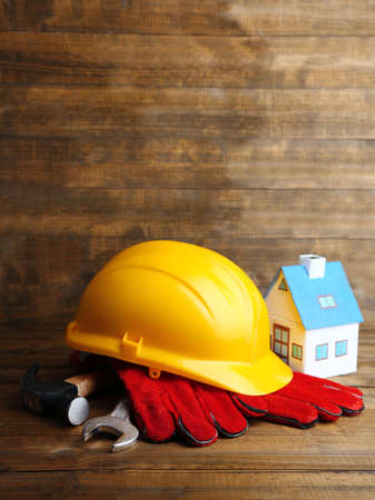Composition with safety helmet, leather gloves, tools and decorative house on wooden background photo