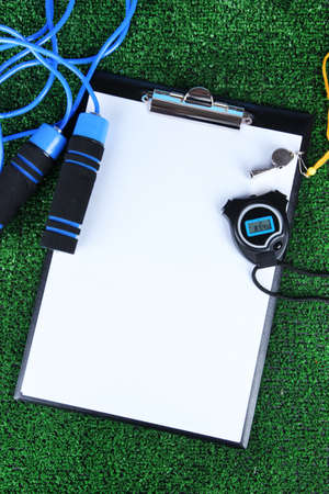 entries: Sheet of paper and sports equipment on grass close-up