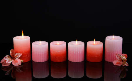 Beautiful candles with flowers isolated on black photo