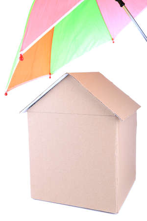 Cardboard house with umbrella isolated on white photo