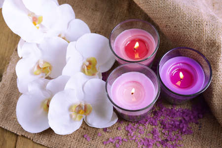 candlelit: Composition with beautiful colorful candles, sea salt and orchid flowers, on wooden background Stock Photo