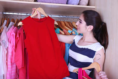 Young woman choose clothes in wardrobe at home photo