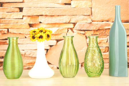 Different decorative vases on shelf on brick wall background photo