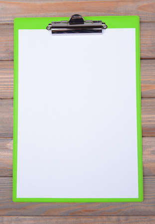 Clipboard on wooden background photo