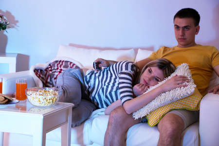 Young couple watching television at home of blacking-out photo
