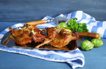 Roasted quails  on tray, on wooden table background photo