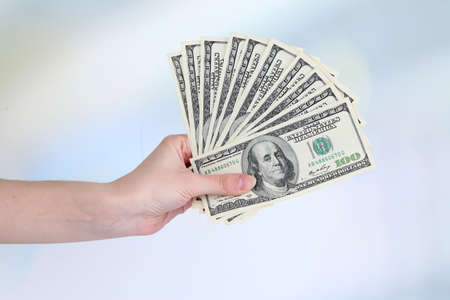 Dollars in hand on bright background