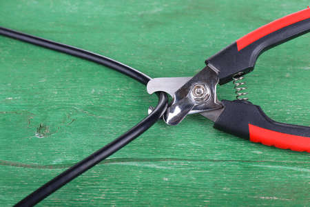 disconnecting: Side cutters cut cable on wooden background