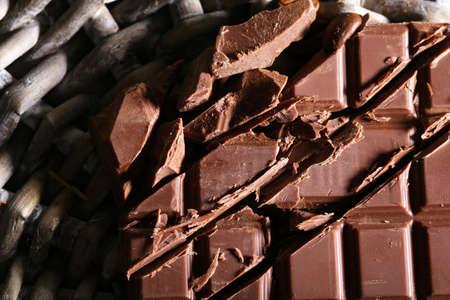 wicker bar: Chopped bar of chocolate on wicker mat background
