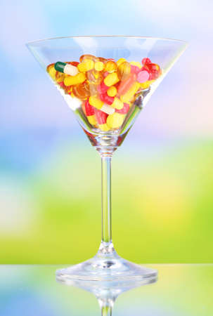 Goblet with pills on natural background photo