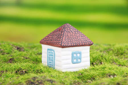 Little house and paper people on green grass, on bright background photo