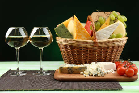 Basket with different cheese and glasses of wine on wooden table, on dark black background photo