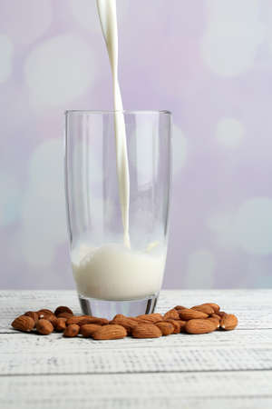 Almond milk is poured into glass, on color wooden table, on light background photo