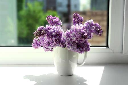 Beautiful lilac flowers on windowsill photo