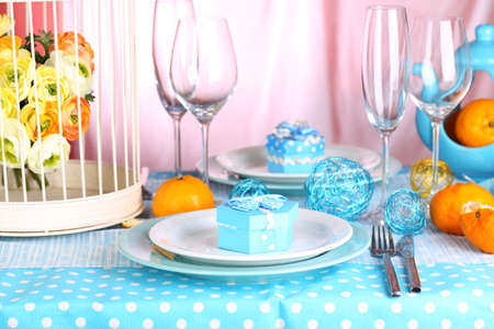 Table serving with colorful tableware on room background photo