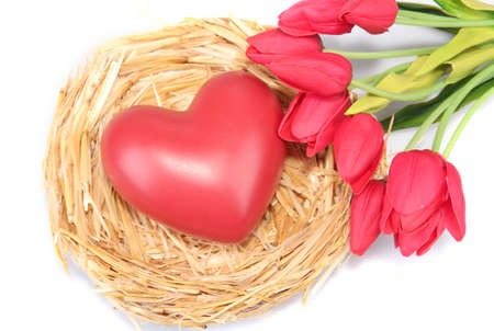 Decorative heart in nest, on color wooden background photo