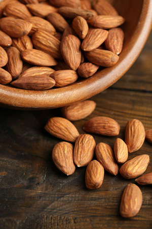 almonds: Almonds in bowl on color wooden background