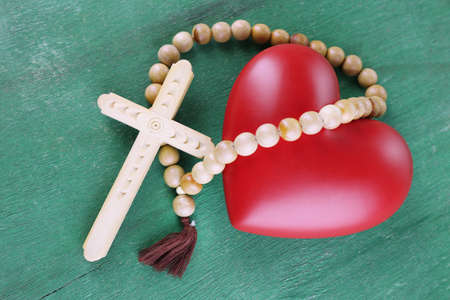 sacrosanct: Heart with rosary beads on wooden background