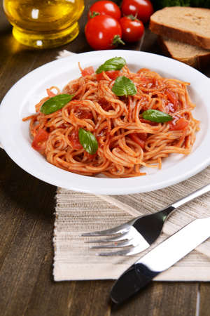 Pasta with tomato sauce on plate on table close-up photo
