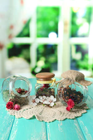 Assortment of herbs and tea in glass jars on wooden table, on bright background  photo