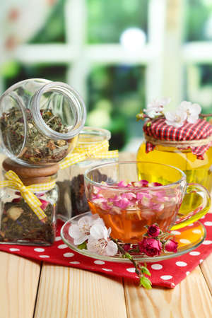 Assortment of herbs, honey and tea in glass jars on wooden table, on bright background  photo