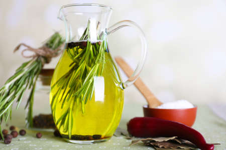 Essential Oil with rosemary in glass jug, on light background photo