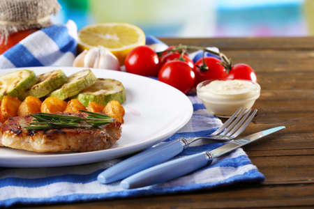 Grilled steak, grilled vegetables and fried potato pieces on table background Фото со стока